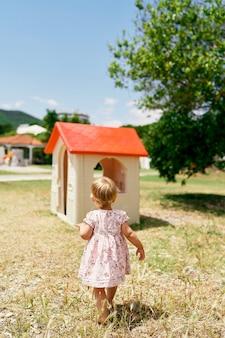 La bambina va alla casa dei giocattoli nella vista posteriore del parco giochi