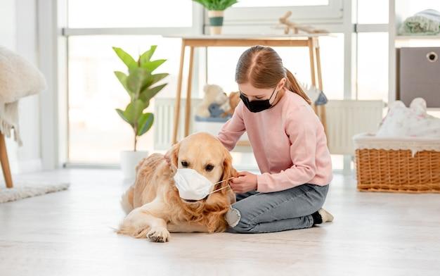 Bambina e cane golden retriever indossando maschere a casa in tempo di pandemia