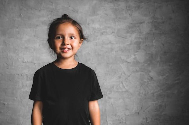 Bambina su uno sfondo grigio. ritratto in bei colori