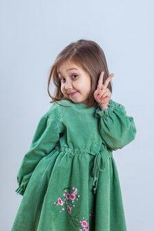 Bambina in abito verde in posa per la fotocamera in studio.