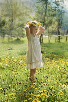 Bambina su erba verde e fiori estivi all'aperto, concetto di pace e felicità