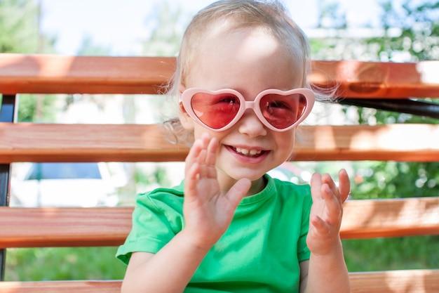 Una bambina con una maglietta verde e occhiali da sole rosa a forma di cuore cammina nel parco in estate