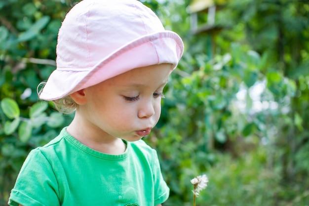 Una bambina con una maglietta verde e un panama rosa cammina nel parco d'estate e succhia il