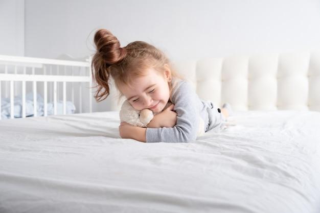 Bambina in dolcevita grigio che gioca con l'orsacchiotto sulla biancheria da letto bianca.