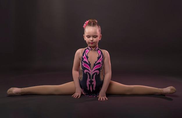 Bambina in costume da ginnasta seduta in spago incrociato o trasversale su sfondo nero per studio