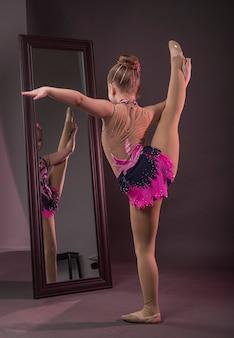Bambina in costume da ginnasta in piedi davanti allo specchio cercando di alzare la gamba per lo spago verticale o...
