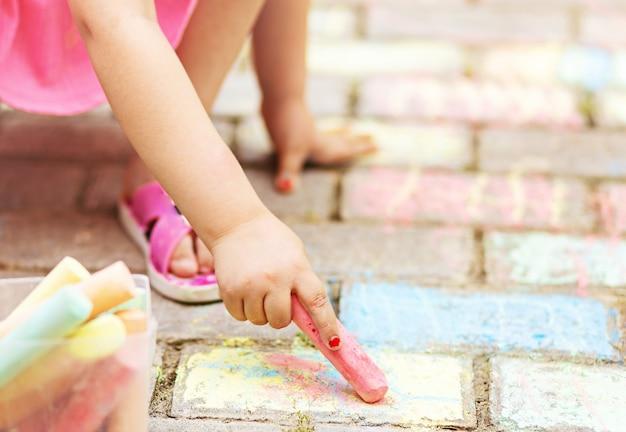 La mano della bambina con un pezzo di gesso colorato disegna su lastre di pavimentazione