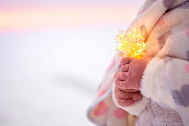 Mani della bambina che tengono stringa di luci bokeh.