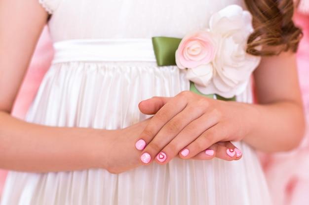 Mani della bambina con manicure, disegno dei cuori