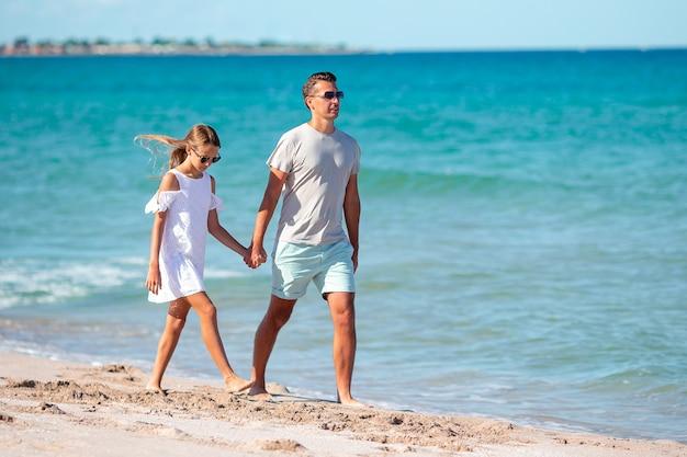 Bambina e papà felice che si divertono durante le vacanze al mare