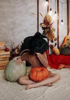 Una bambina si è coperta il viso con un cappello da strega ed è seduta su una coperta a maglia con delle zucche