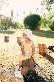 La bambina con un cappello si siede su un ceppo d'albero girando la testa di lato