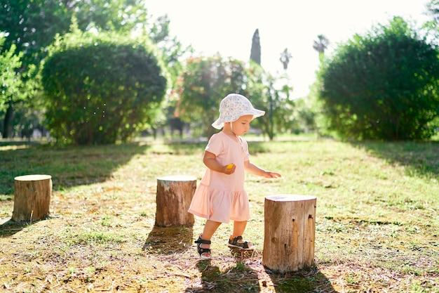 La bambina con un cappello sta sul prato vicino ai ceppi