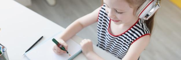 Bambina in cuffia seduta davanti al computer portatile e scrivendo sul taccuino