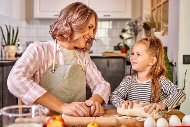 Bambina e sua mamma in grembiule che impastano la pasta in cucina, pasticceria fatta in casa per pane, pizza o biscotti da forno. divertimento in famiglia e concetto di cucina