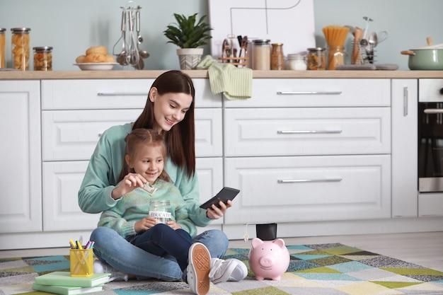 Bambina e sua madre con i risparmi per l'istruzione a casa