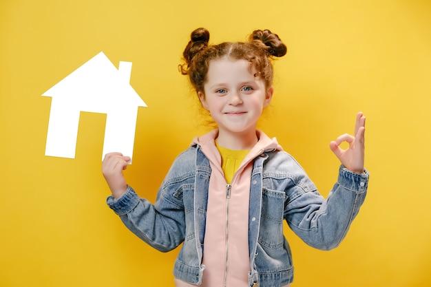 La bambina tiene una piccola casa di carta e fa il segno ok isolato su sfondo giallo