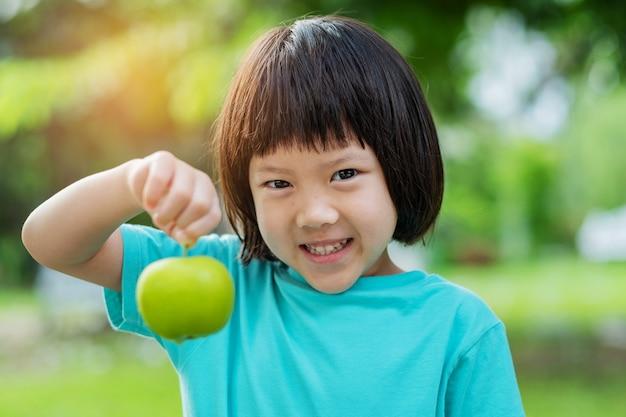 Bambina che tiene una mela con sfondo verde natura