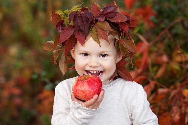Bambina che tiene le mele nel giardino autunnale nutrizione sana tempo di halloween e del ringraziamento