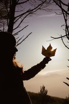 Bambina che tiene foglia d'autunno al tramonto