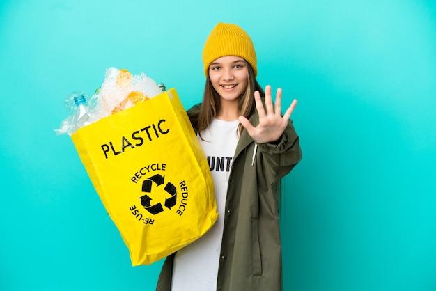 Bambina che tiene una borsa piena di bottiglie di plastica da riciclare su sfondo blu isolato contando cinque con le dita