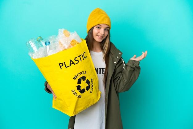 Bambina che tiene una borsa piena di bottiglie di plastica da riciclare su uno sfondo blu isolato che allunga le mani di lato per invitare a venire