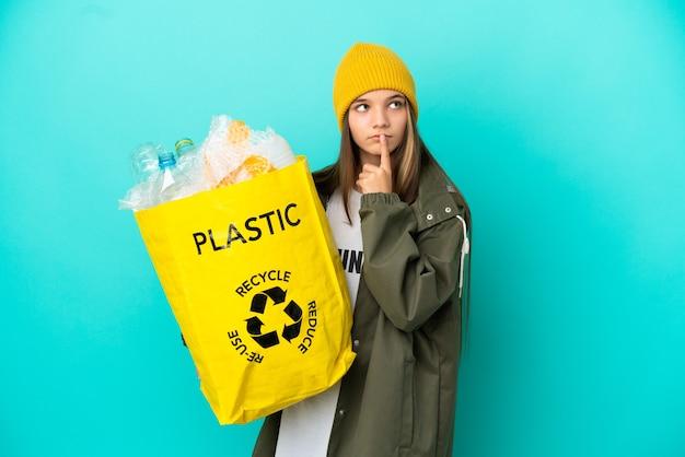 Bambina che tiene una borsa piena di bottiglie di plastica da riciclare su sfondo blu isolato avendo dubbi mentre guarda in alto