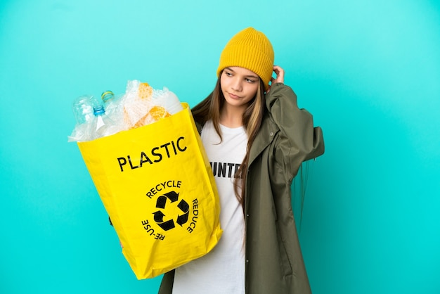 Bambina che tiene una borsa piena di bottiglie di plastica da riciclare su sfondo blu isolato avendo dubbi