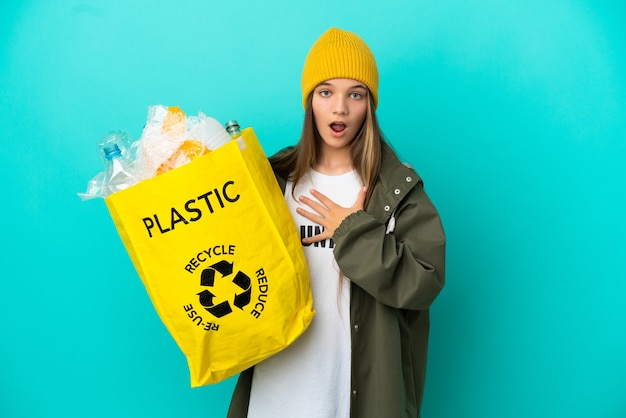 Bambina che tiene una borsa piena di bottiglie di plastica da riciclare su sfondo blu isolato sorpresa e scioccata mentre guarda a destra looking