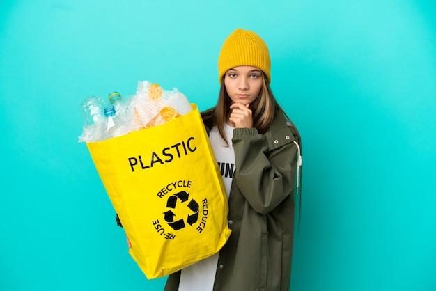 Bambina che tiene una borsa piena di bottiglie di plastica da riciclare su sfondo blu isolato pensando