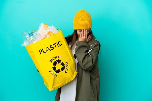 Bambina che tiene una borsa piena di bottiglie di plastica da riciclare su sfondo blu isolato con espressione stanca e malata