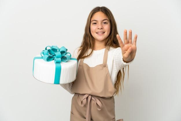 Bambina in possesso di una grande torta su sfondo bianco isolato felice e contando quattro con le dita