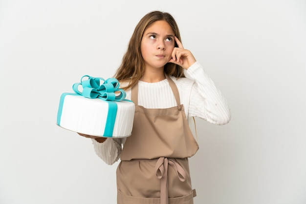 Bambina che tiene una grande torta su sfondo bianco isolato avendo dubbi e pensando