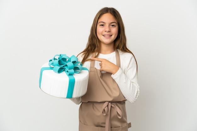 Bambina che tiene una grande torta sopra bianco isolato che indica al lato per presentare un prodotto
