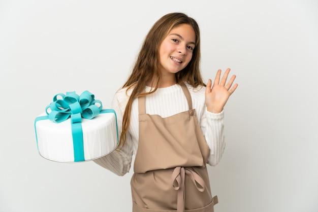 Bambina che tiene una grande torta sopra bianco isolato che saluta con la mano con l'espressione felice
