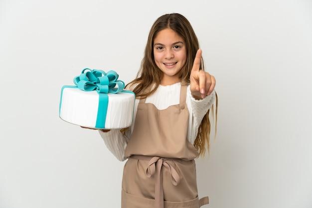 Bambina che tiene una grande torta sopra la rappresentazione bianca isolata e che alza un dito