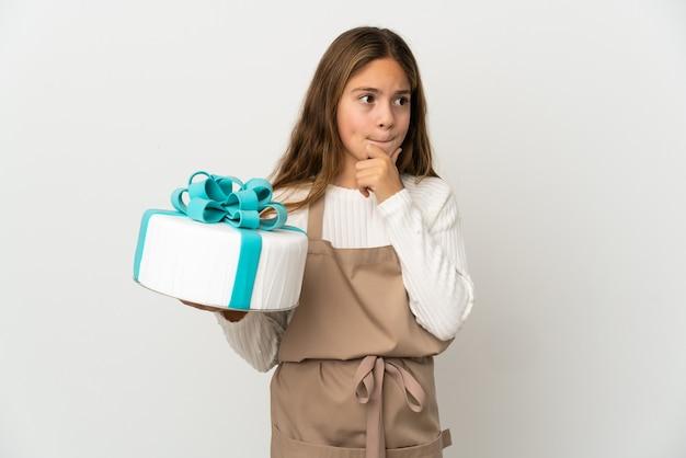 Bambina che tiene una grande torta sopra la parete bianca isolata che ha dubbi e che pensa