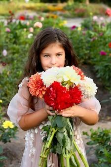 Bambina con bouquet di fiori di dalie. bambino che gode della natura.