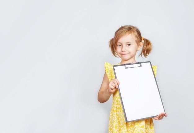 Bambina che tiene un blocco per appunti con un foglio bianco