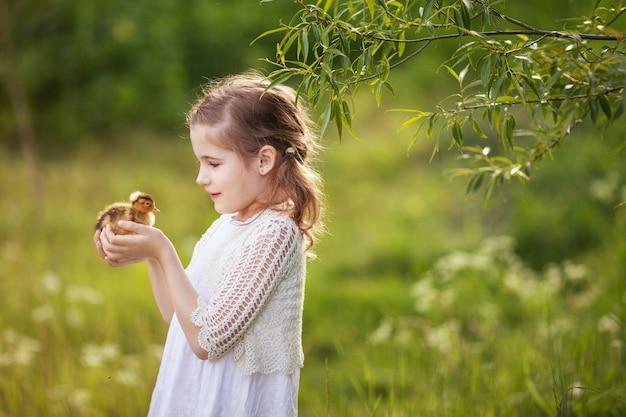 Bambina che tiene un simpatico anatroccolo nelle mani.