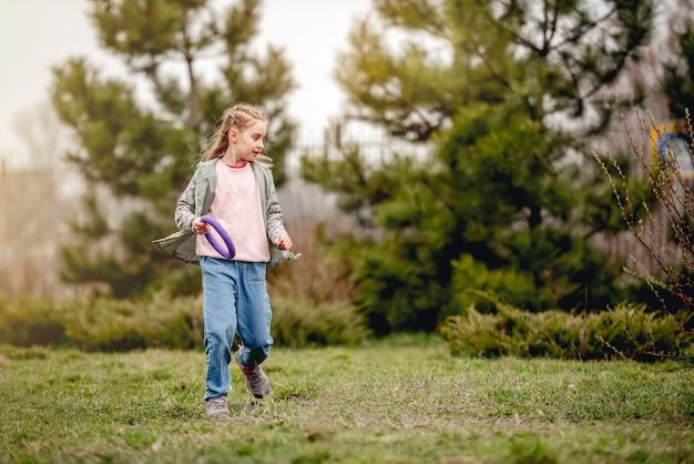 Bambina che tiene in mano un anello giocattolo alla pecorina per allenarsi durante la passeggiata con il cane
