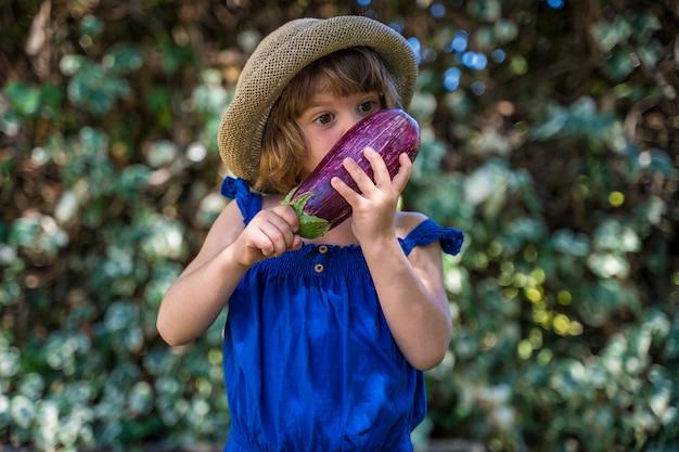 Bambina che tiene una melanzana di eco