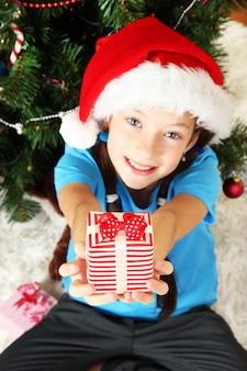 Bambina con scatola regalo vicino all'albero di natale