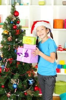 Bambina che tiene scatole regalo vicino all'albero di natale