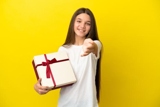 Bambina che tiene un regalo su sfondo giallo isolato che stringe la mano per aver chiuso un buon affare