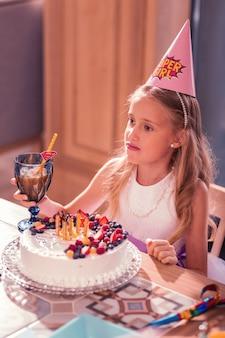 Bambina che tiene un bicchiere di succo con torta di compleanno