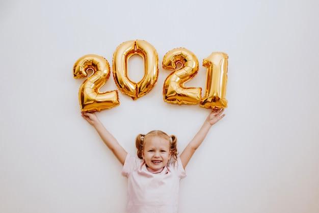 Bambina che tiene palloncini dorati con numeri d'oro