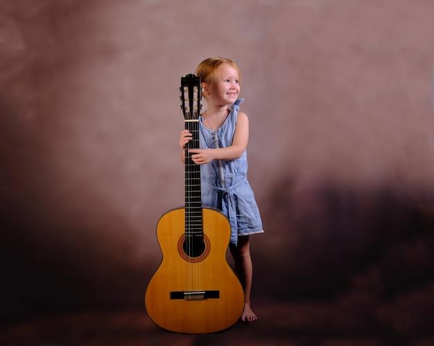Bambina in possesso di una chitarra con un sorriso sul viso. educazione dei bambini e concetto di occupazione.
