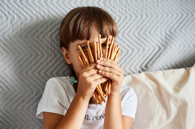 Bambina che tiene in mano e copre il viso con bastoncini di biscotti, bambina sconosciuta dai capelli scuri che indossa una maglietta casual bianca, seduta sul divano, guardando attraverso i salatini.