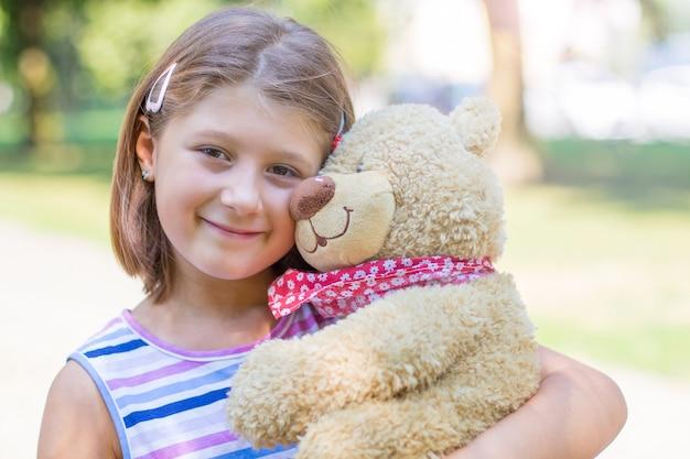 Bambina che tiene un grande orsacchiotto fuori